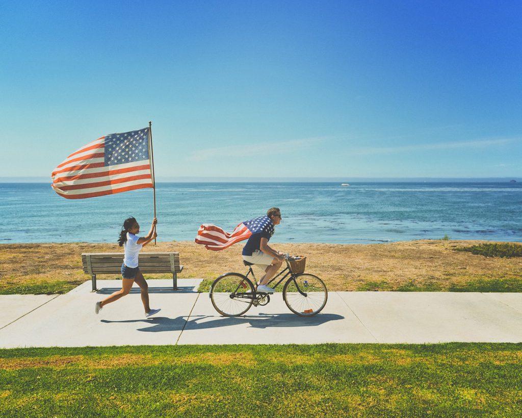 アメリカの国旗を掲げて自転車に乗る人々がビーチを行く